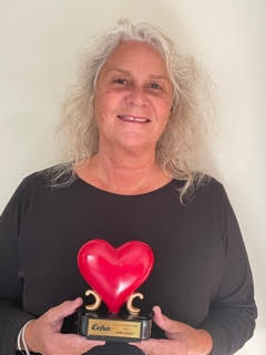 A portrait photo of Anne Goslett holding a trophy that features a big red heart.
